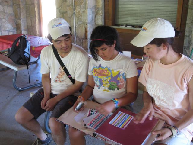 Jennifer Rodriguez shows her scrapbook to Japanese studying grief counseling at Camp El Tesoro near Granbury.