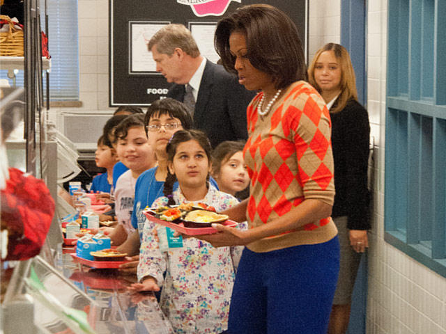 A student at Virginia's Parklawn Elementary School assists First Lady Michelle Obama with her lunch selection. Tonight, the First Lady will be at a Fort Worth Olive Garden for a roundtable discussion on health.
