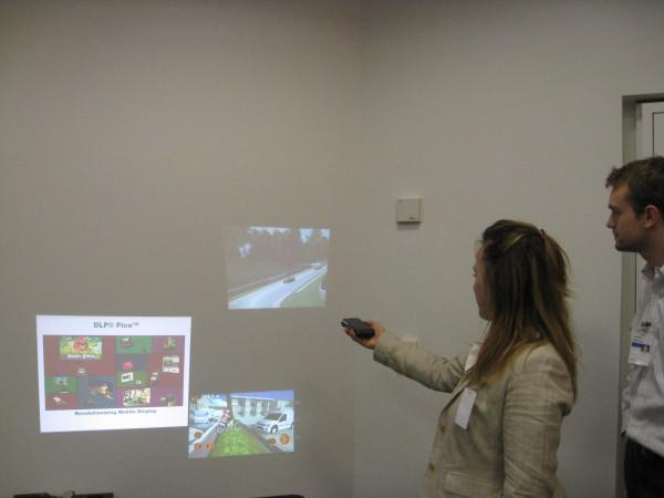 TI workers demo of computer game projected through smart phone