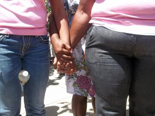 Women outside Dixon Circle Missionary Baptist Church clasp hands in prayer.