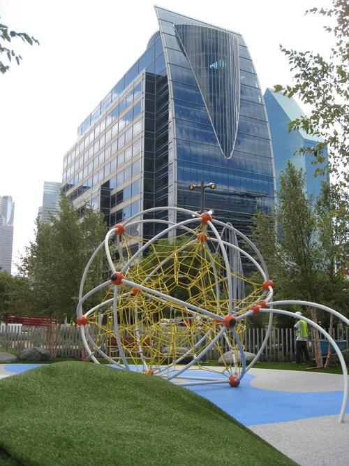 Playground equipment sits beneath downtown Dallas skyscrapers in the Klyde Warren Park.