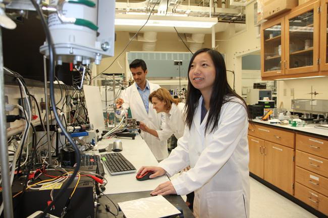 At UT Dallas's NanoTech Institute, research associates Dr. Márcio Dias Lima and Dr. Monica Jung de Andrade adjust an apparatus that tests the strength of a carbon nanotube yarn, while graduate student Na Li monitors the results.