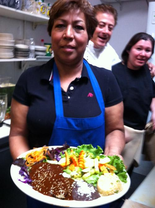 Maria Rodriguez hold plate of Chicken Mole while Pedro Capistran and Aurelia Cervantes look on in the kitchen at Veracruz restaurant.