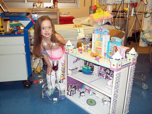 "Kenedi Groves, 7, poses with her handmade dollhouse at Children's Medical Center in Dallas. She's wired up to an artificial ""Berlin"" heart while she awaits a transplant."