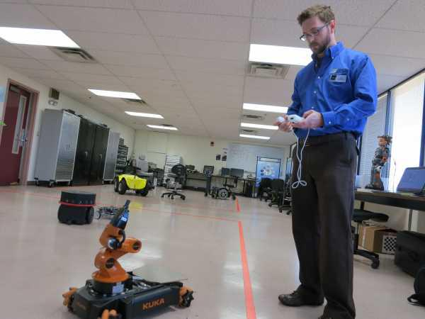 Graduate student Joe Sanford controls a KUKA robot using a Wii game controller. In addition to adding sensors, researchers at UTARI are helping to develop more delicate motor functions for robots.