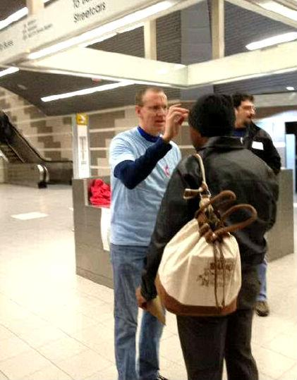 Scott Collin places ashes on a commuter's forehead at a downtown DART station.
