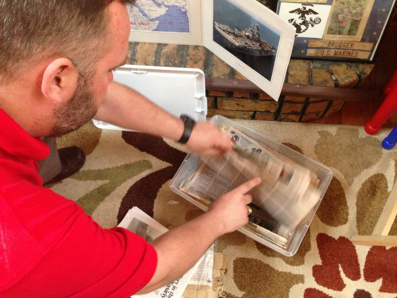 Marine and Iraq war vet Dion Brugger flips through newspaper clippings his mother saved while he was in Iraq.