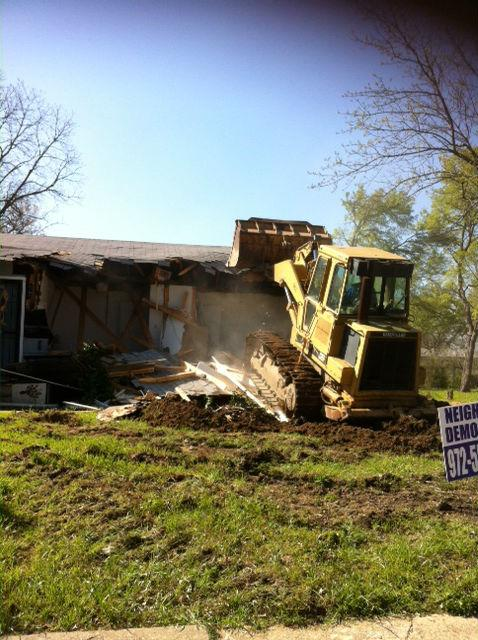 A bulldozer takes down a drug house on Life Avenue in  West Dallas. It and four other properties on the block were once owned by the Gator Boyz, a local gang prosecutors said terrorized the neighborhood.