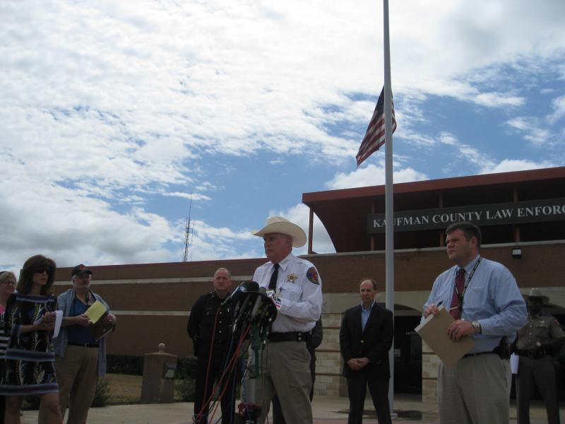 Kaufman County Sheriff David Byrnes, in front of Kaufman flags at half staff, talking about County District Attorney Mike McLelland. McLelland and his wife were killed by unknown gunmen Saturday