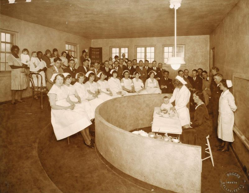 A classroom inside the Bradford Hospital -- May  Smith is at the front, looking down at the baby.