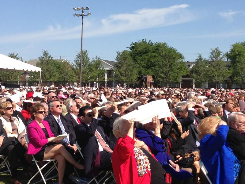 Some in the audience used their programs as sun shields during the library dedication ceremony.