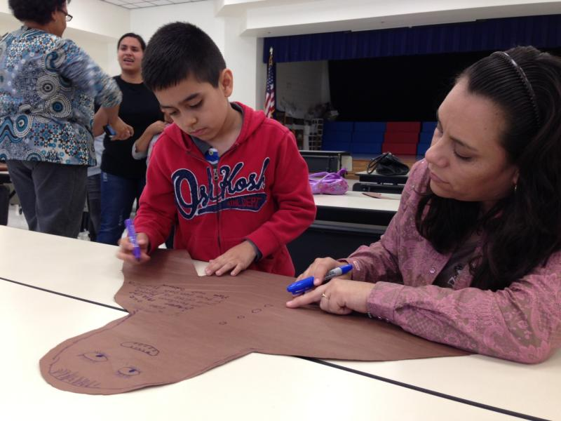 Second-grader David Zavala works with his mom to write a message for the children in the town of West.