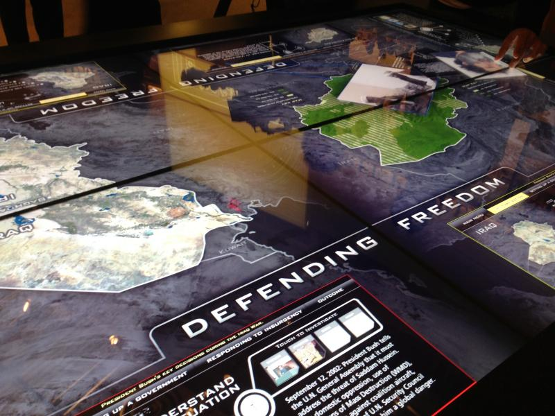 "One of the interactive displays at the musuem is called ""Defending Freedom."" It looks like a giant glass-topped tablet which you can use to pull up photos, documents and maps to learn about the invasion of Iraq."