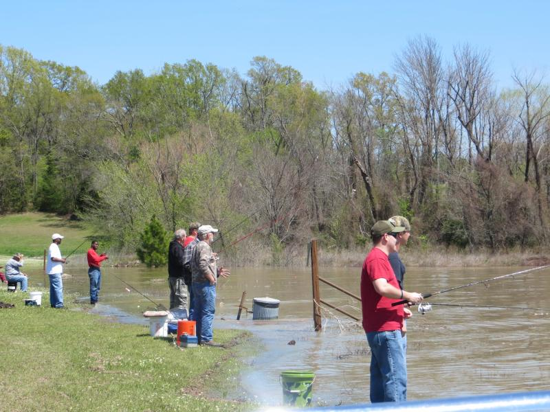 Fishermen line the banks of the Kiamichi River.