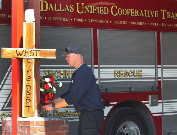 Mark Pozsgai, a Cedar Hill firefighter, places roses at a cross at the West Volunteer Fire Department.
