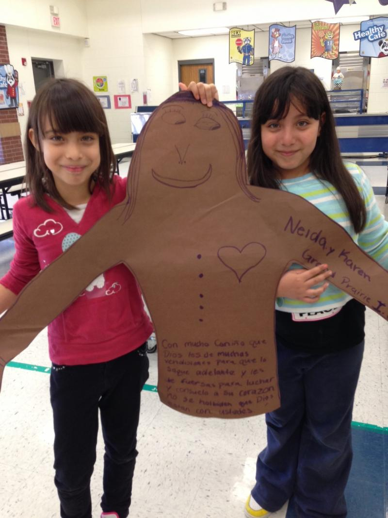 """Neida and Karen Pleitez, ages 7, show off their """"gingerbread person"""" they created with the help of their mom."""