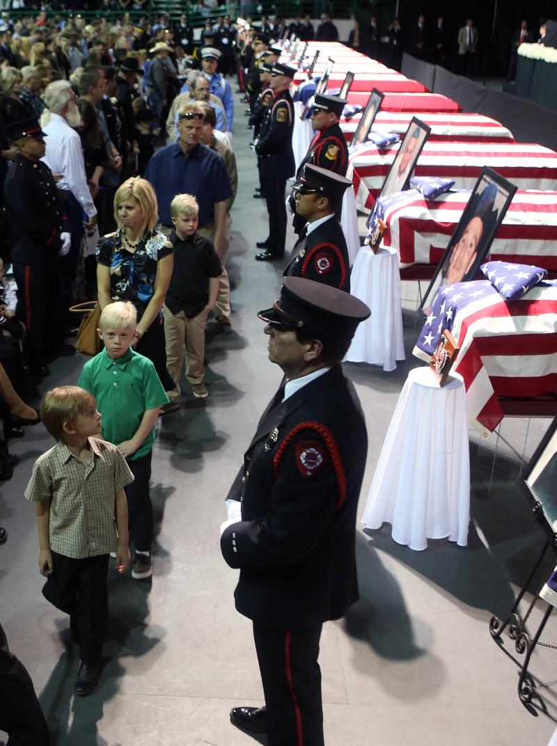 The caskets of first responders killed in the explosion brought thousands to a memorial service.