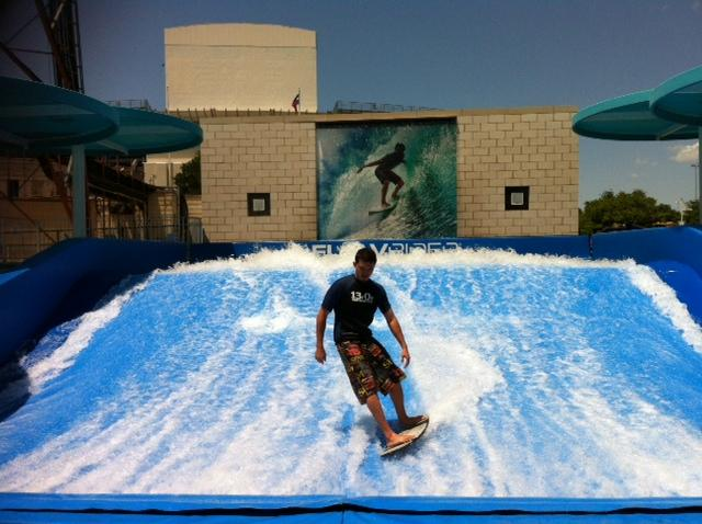 An instructor rides the wave at Fair Park's Summer Adventures. Midway goers body surf, belly on a board.