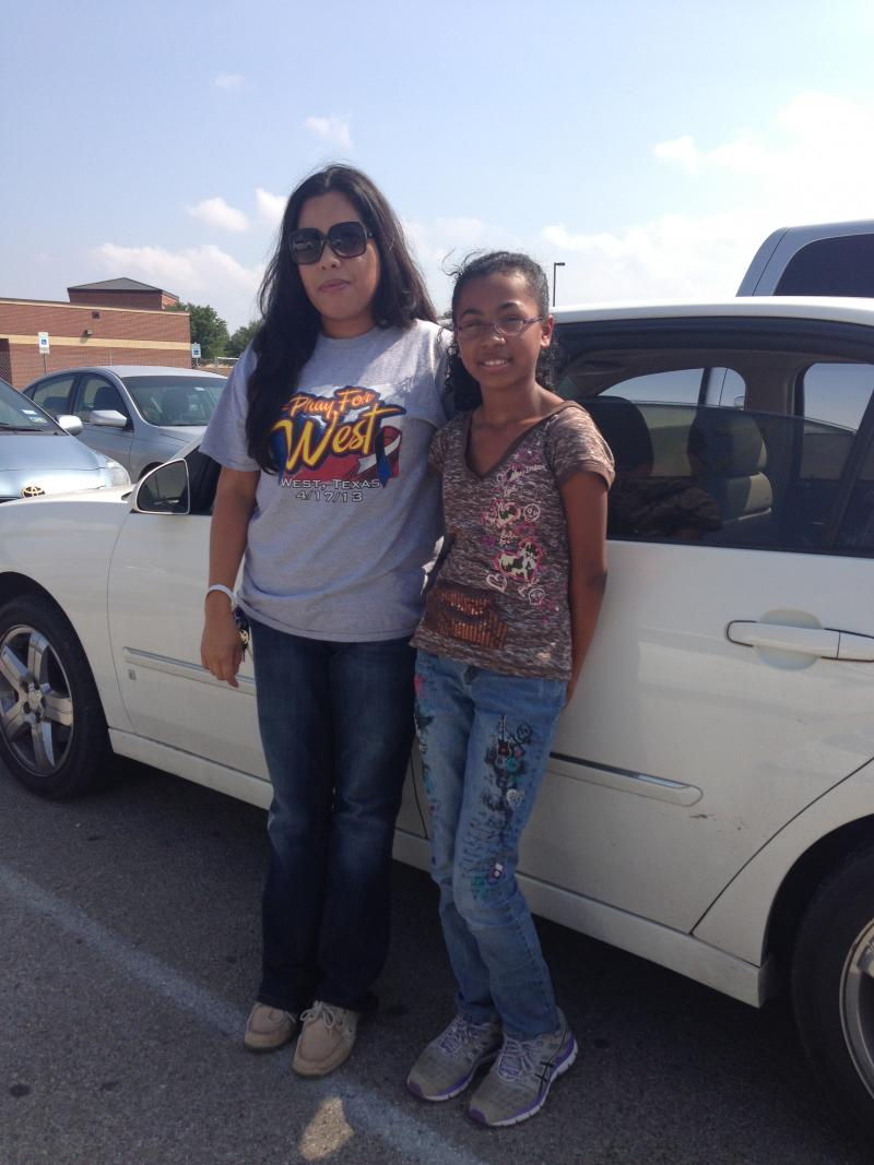 Glora Alamos and her daughter, Brianna, in the West High School Parking Lot awaiting news from federal agents on the cause of the fire and explosion that destroyed their home.