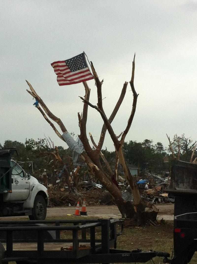 An American flag flies from one of the trees in Rancho Brazos, the Granbury neighborhood decimated by a tornado Wednesday night. Winds of up to 200 mph also stripped trees of their leaves.