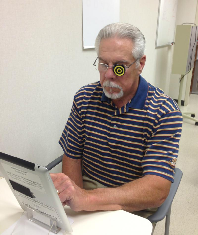 Patient Daniel Agnew of Frisco using the MyVisionTrack app for the first time at the Texas Retina Associates. The camera in the iPad is programed to identify the yellow and black eye patch he's wearing to verify that he's tested both left and right eyes.