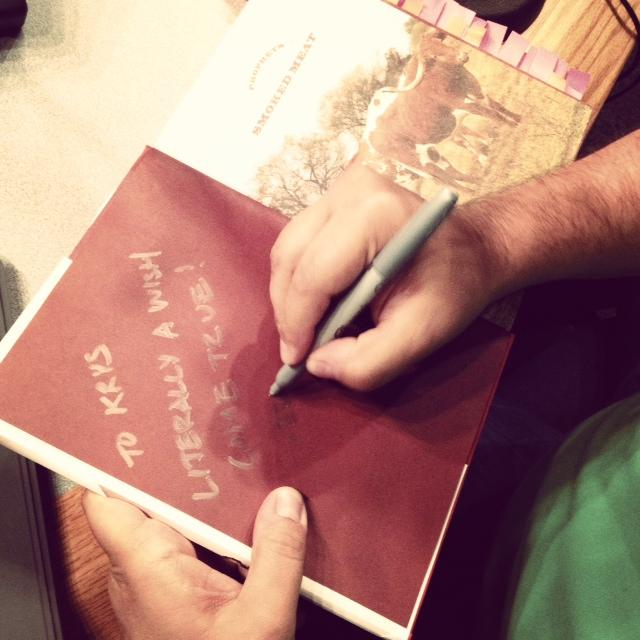 Daniel Vaughn signs 'Think' host Krys Boyd's tabbed-up copy of his book, 'The Prophets Of Smoked Meat.'