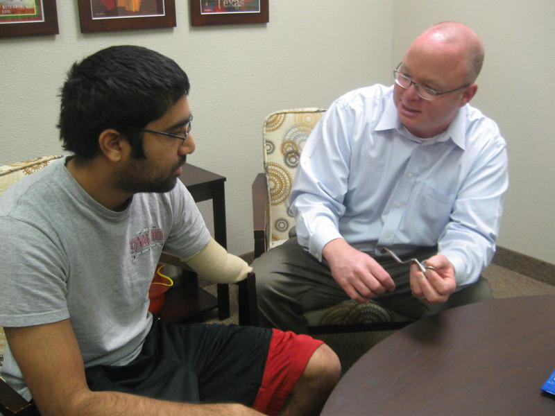 Chris Lake (r) shows Amar Patel an adapted dental tool designed to work with Patel's prosthetic hand.