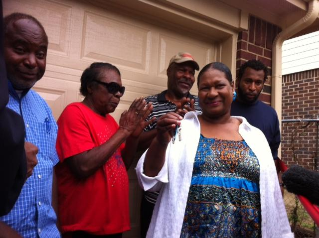 Dora Fuller, (right-front) holds the keys to her new home on Berwick Avenue.