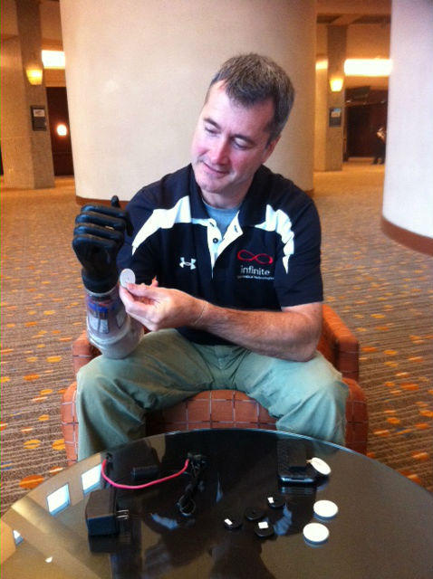 Sean McHugh prepares to swipe a wrist band RFID 'reader' installed in his prosthesis with an RFID chip programmed to open his hand.