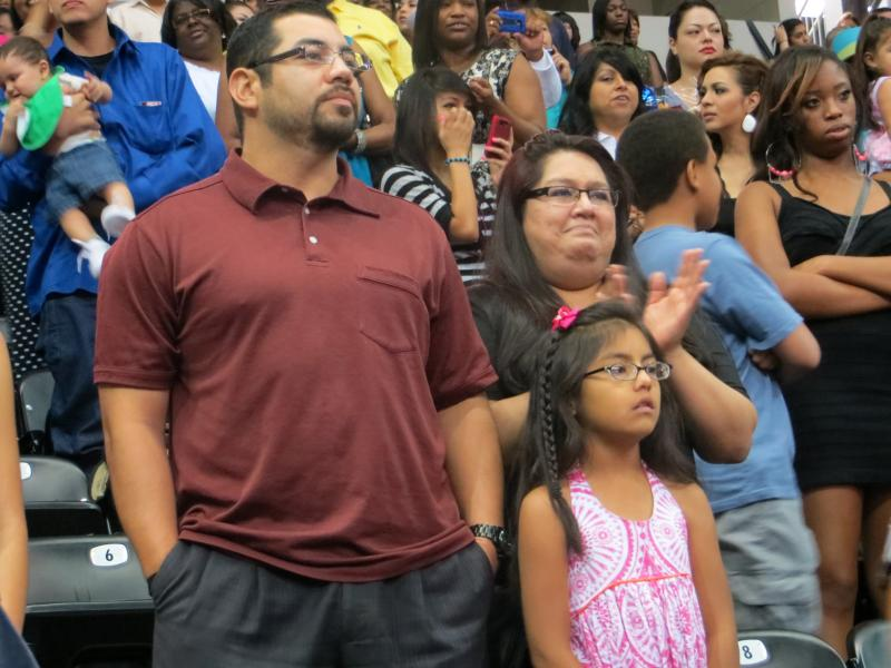 Richard Flores' uncle, mother and sister proudly watch him graduate.