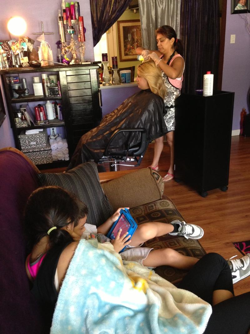 Nelly, Alex's older sister colors a friend's hair while Alex and her nephew Norman check out a game on his tablet.
