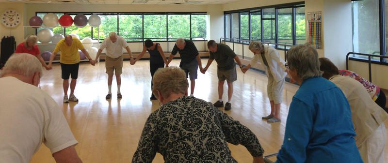 At the end of the dance class for people with movement disorder patients, students gather in a circle and take a final bow.