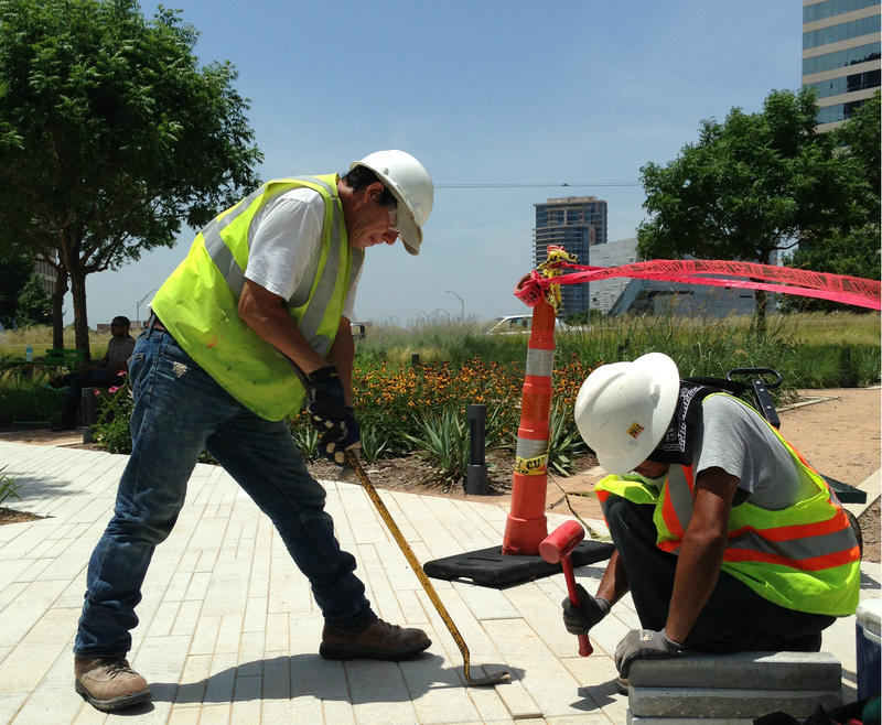 Texas Department of Transportation workers Carlos De La Torre (left) and Fabian Morales say they're taking more breaks than usual to avoid heatstroke.