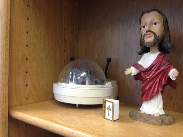 A robot John Dyer made when he was younger sits casually next to a Jesus bobblehead in his office.