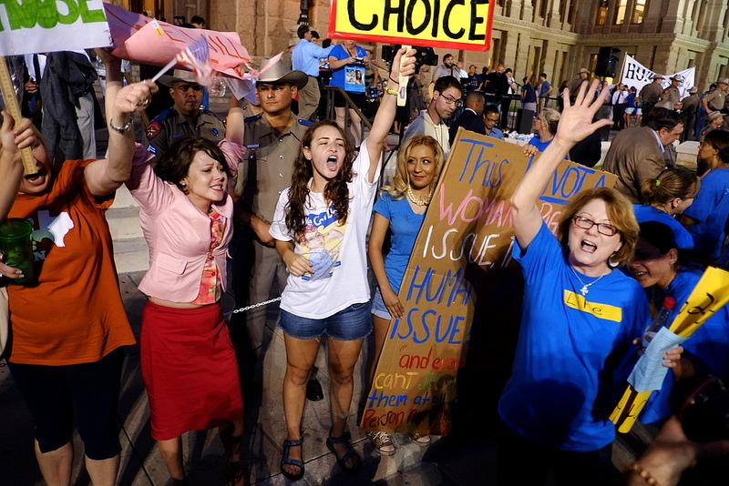 Blue-clad supporters of abortion restrictions square off with orange pro-choice opponents on the Capitol steps Monday.