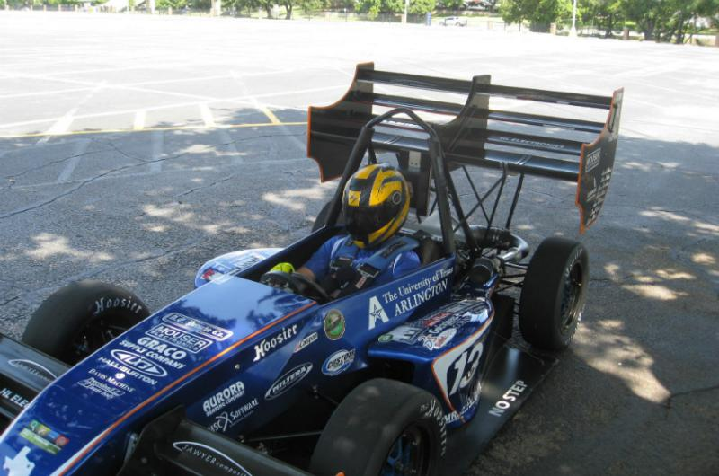 JP Merkel behind the wheel of UTArlington's mini Indy car with wings Merkel designed
