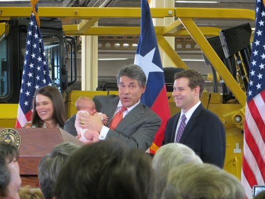 Gov. Rick Perry shows off his new granddaughter at event where he made announcement that he won't run again for Texas governor.