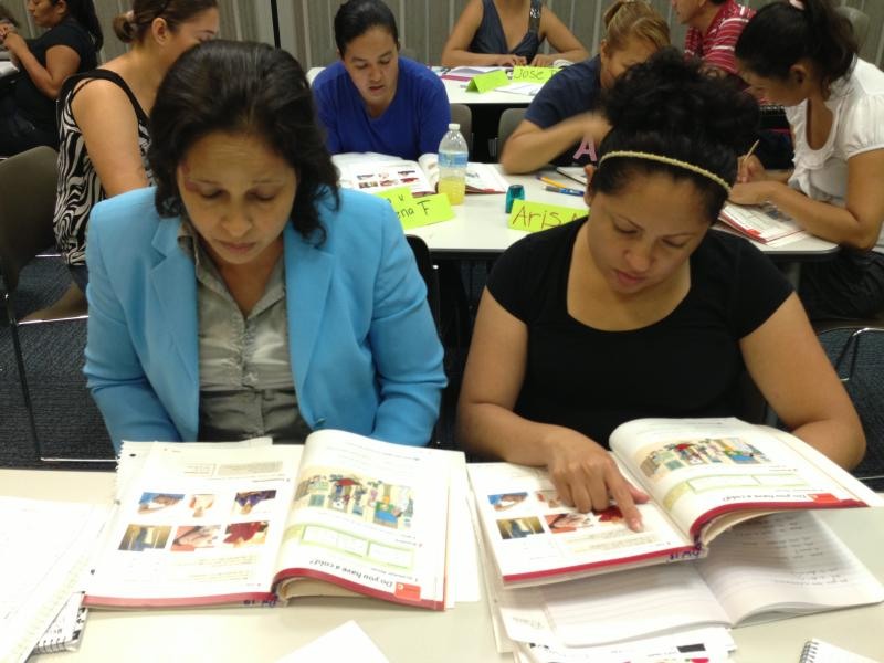 Martha Ayala and Irma Rivera study an English language instruction book during a class at the West Dallas Public Library branch. The library houses the new Atmos Energy Literacy Center.