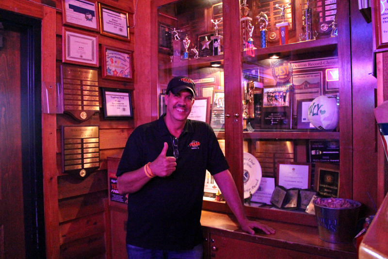Riki Rijos, Sr., in front of the trophy case of local teams,  in his Texas Roadhouse restaurant, near UNT's campus. Dad used to play basketball and is heavily involved with his son's basketball pursuits and does some coaching too