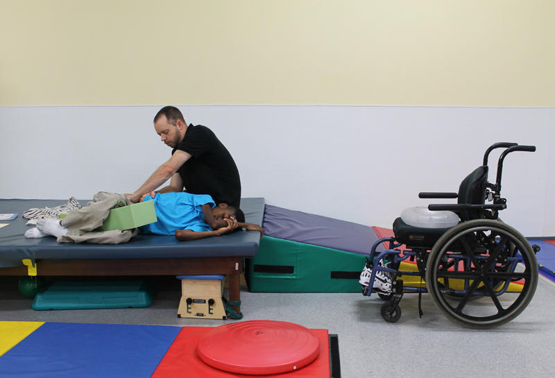 Nathan Morgan applies pressure to some areas of Chance's body and helps him stretch as part of the treatment for his muscular dystrophy disorder. The therapy helps Chance relax and feel more comfortable.