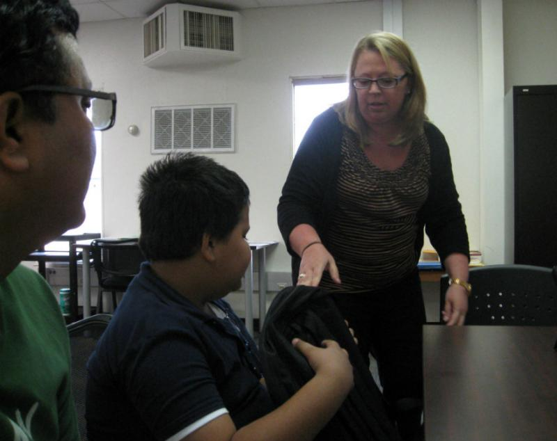 DISD Intake Specialist April May handing free, supply-filled backpack to Ayush Kafley. All Intake Center kids get one