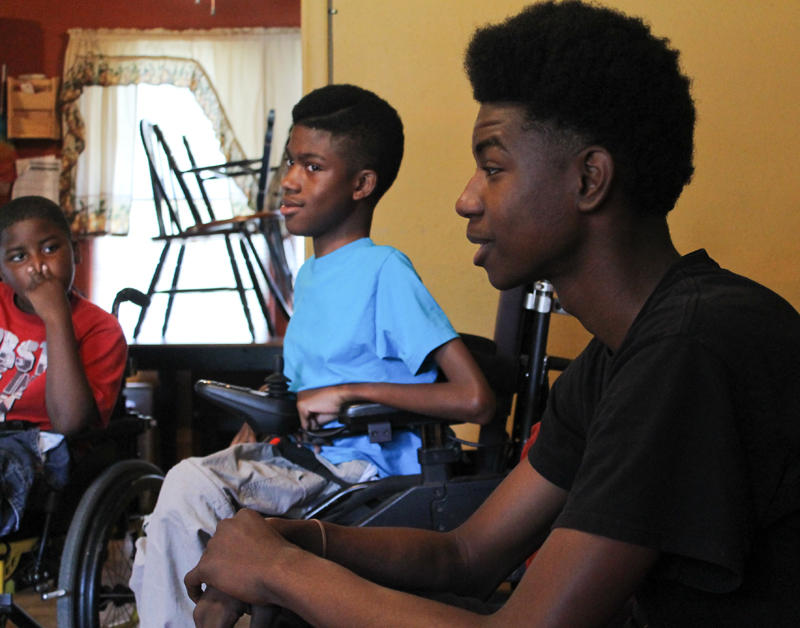Chance hangs out with two of his brothers, Robert (right) and Louis Jr., in their living room.