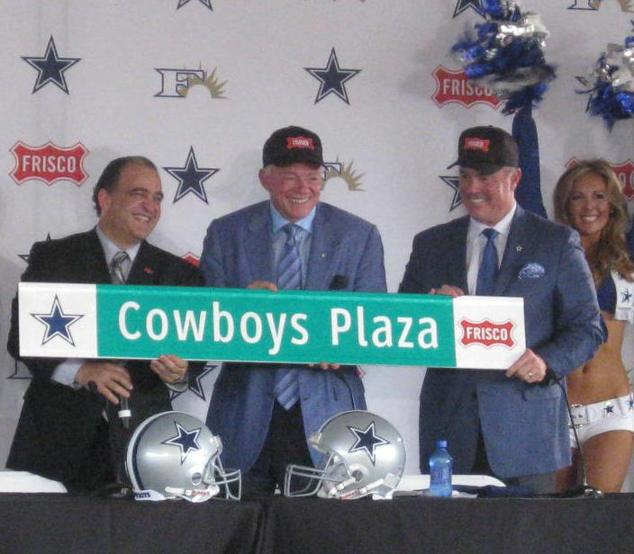 Frisco Mayor Maher Maso, l, welcoming Cowboys owner Jerry Jones and son Stephen to Frisco with the gift of a sign.  Cheerleaders were on both sides.