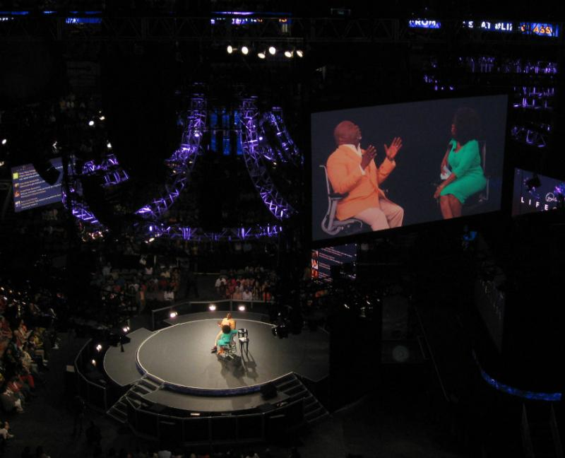 Bishop T.D. Jakes with Oprah Winfrey in front of thousands who could also watch the two on several giant screens at the American Airlines Center in Dallas. The two were taping Winfrey's Lifeclass cable show about fatherlessness