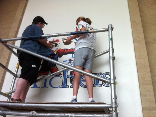 Volunteers work on the large Atwell mascot mural in the school's lobby.