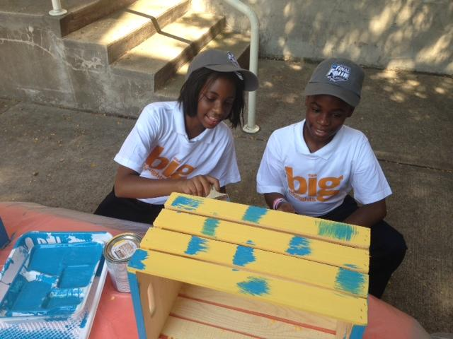 These crates will become bookshelves for kids in need, and the students at Charles Rice Learning Center are happy to paint them.