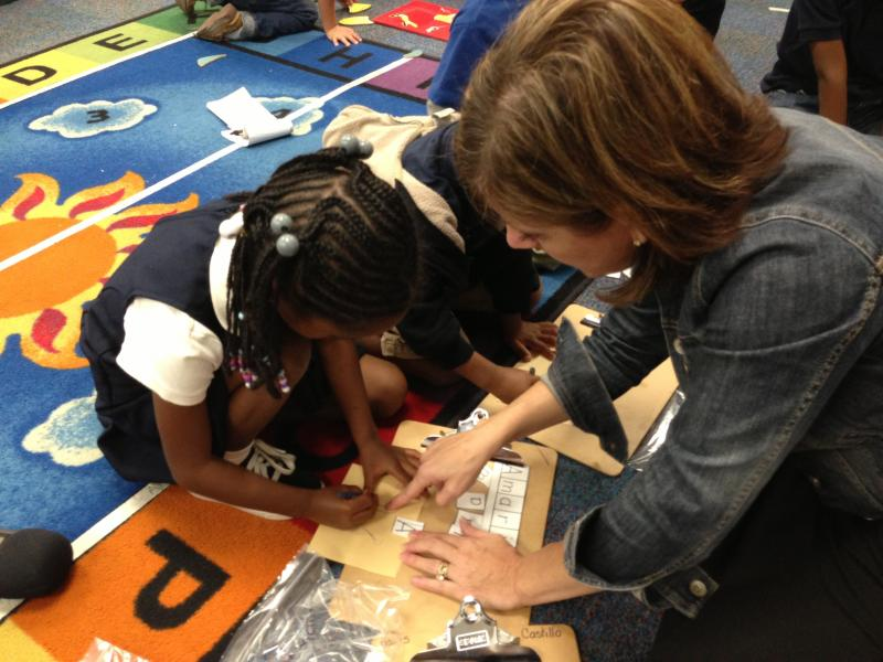 Pre-K teacher Misty Hollis helps student Amari Rowe write the letter A.