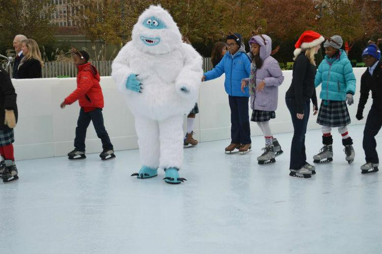 Bumble, the abominable snowman, skated with some students Friday at the new ice skating rink at Klyde Warren Park.