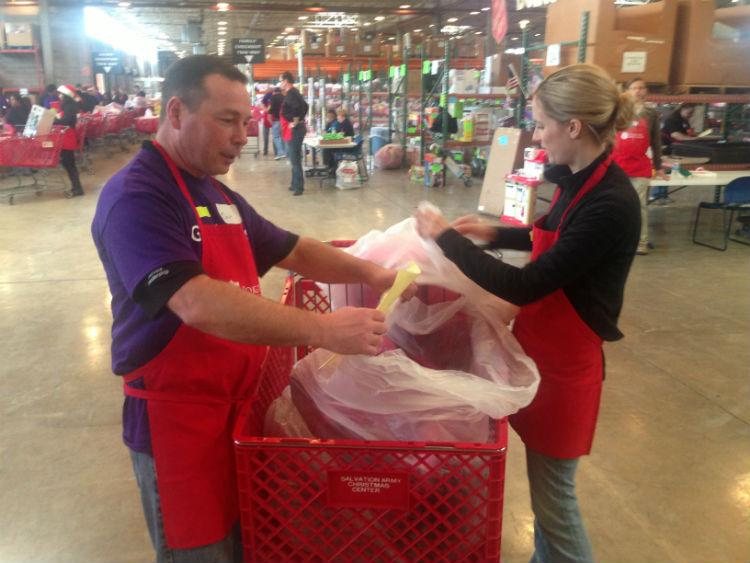 Volunteers check bags in shopping carts before handing off the toys to needy families.