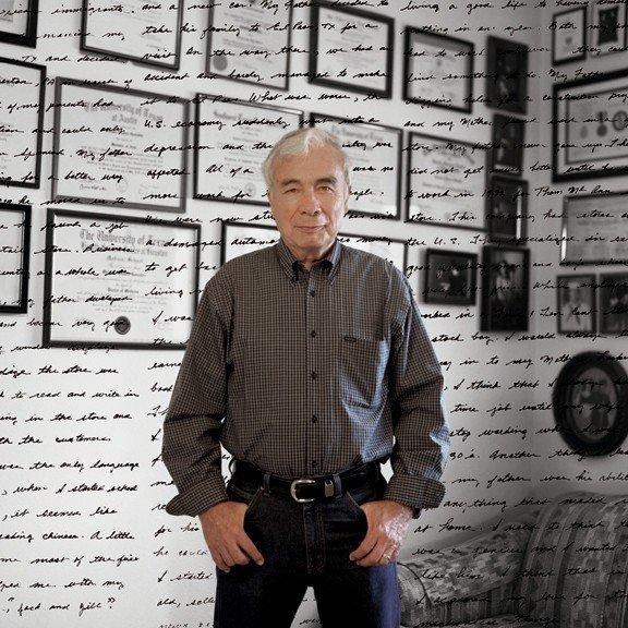 Arthur Charles Gonzalez Sr. poses in front of a wall of degrees earned by his family members.